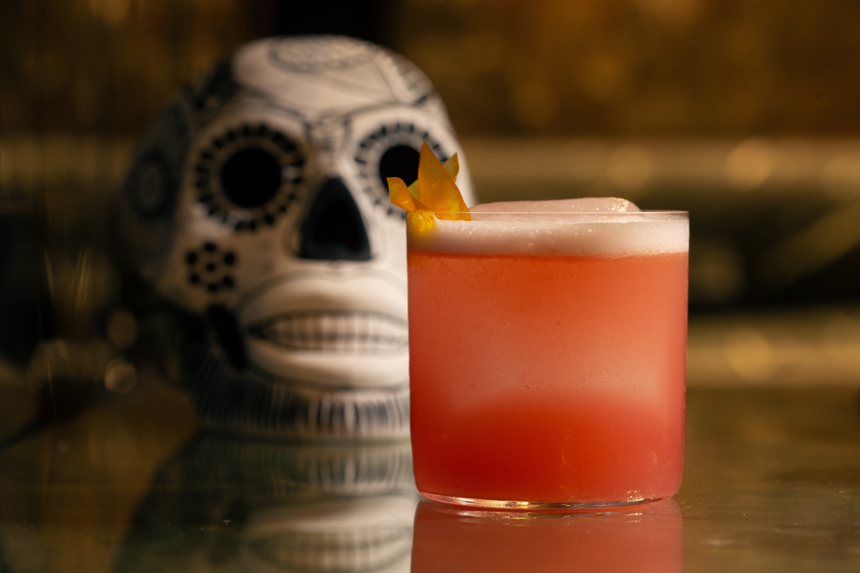 Red La Catrina cocktail near a day of the dead skull.