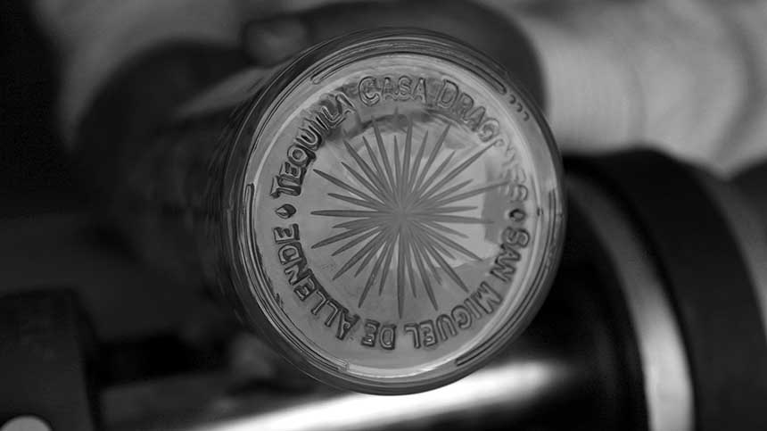 The full engraved bottom of a Tequila Casa Dragones bottle. Engraving states ' Tequila Casa Dragones. San Miguel de Allende'.